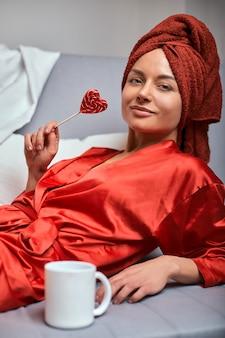 赤いバスローブとソファーに赤いタオルとコーヒーマグとロリポップをモデル化します。ファッションのコンセプト、色のゲーム、ミニマリズム。仕事から休み、残りの時間。