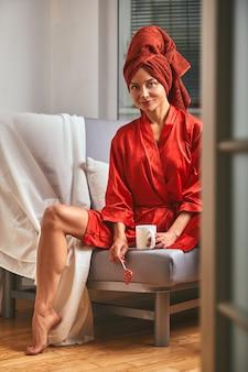 커피 머그잔과 롤리팝으로 소파에 빨간 목욕 가운과 빨간 수건을 입은 모델. 패션의 개념, 색상의 게임, 미니멀리즘. 직장에서 쉬고, 쉬는 시간.