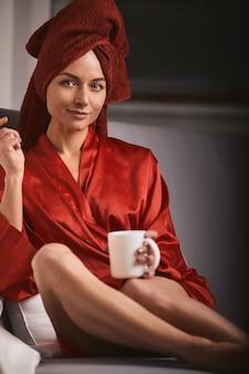 빨간 목욕 가운을 입고 소파에 빨간 수건과 커피잔과 막대 사탕을 입은 모델입니다. 패션의 개념, 색상 게임, 미니멀리즘. 퇴근, 휴식 시간.