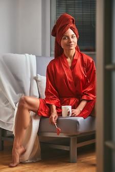 赤いバスローブとソファーに赤いタオルとコーヒーマグとロリポップをモデル化します。