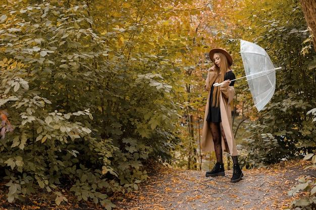 Модель в осенней одежде с прозрачным зонтиком возле осеннего фона. свободное место для текста