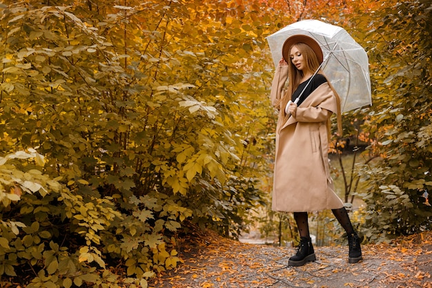 Модель в осенней одежде с зонтиком в осеннем парке. свободное место для текста. осенние тенденции