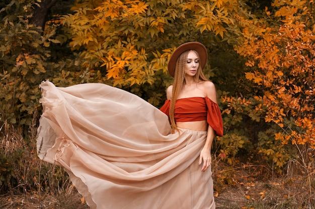 美しい秋の服と紅葉の秋の化粧と茶色の帽子のモデル
