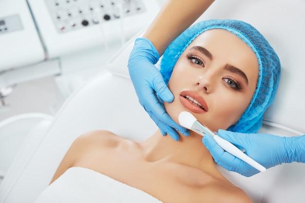 소파에 누워 파란 모자 모델. 브러시로 그녀의 얼굴을 만지고 파란색 장갑에 의사의 손. 머리와 어깨, 머리와 어깨, 미용