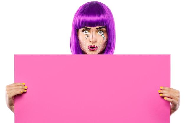 팝 아트 메이크업과 창의적인 이미지의 모델은 흰색에 고립 된 핑크 빈 보드를 들고있다