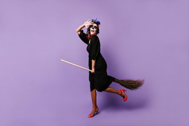 Модель в образе ведьмы, счастливо позирует, сидя на метле. женщина развлекается в своем наряде на хэллоуин.