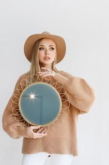 灰色の背景に鏡と化粧をしたスタイリッシュな秋の服のモデル。クリエイティブ