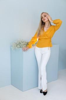繊細な背景にスタイリッシュな服のブロガーのモデル