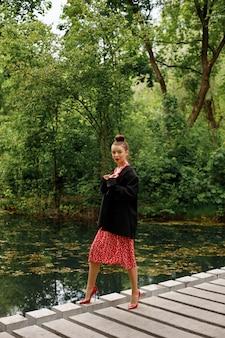 公園で夏の散歩にスタイリッシュな服を着たモデル。赤い靴、赤いドレス、黒いジャケット。唇は赤い口紅で塗られ、髪が集められます。