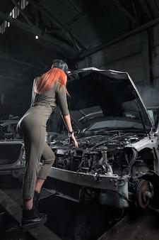 ガレージの分解された車の開いたボンネットの上に立っているスタイリッシュな服のモデル。