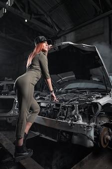 Модель в стильной одежде стоит на открытом капоте в разобранном автомобиле в гараже.