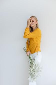 単色の背景に花を手にしたスタイリッシュな服のモデル。秋の画像