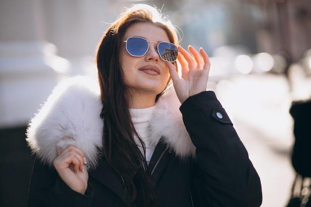 通りでポーズをとっているサングラスのモデル