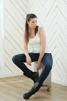 Модель в белом спортсмене, джинсах и кожаных сапогах