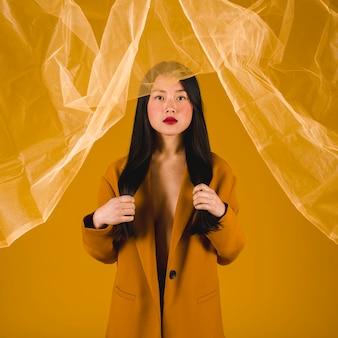 黄色の背景と黄色のコートを着たモデル