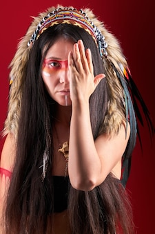 Model in indian wearing and colorful makeup posing , with feathers on head. indigenous peoples of the americas outfit, ethnic woman closing half of face