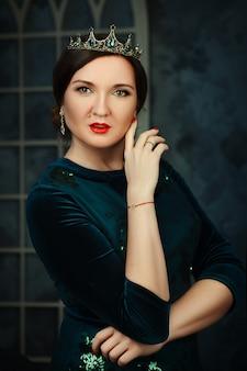 Model is posing in a dark studio as a queen