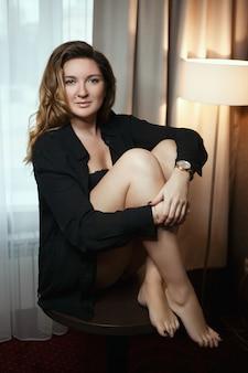 モデルはホテルの部屋でポーズをとっている