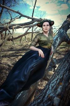 Модель позирует в весеннем лесу как фавн