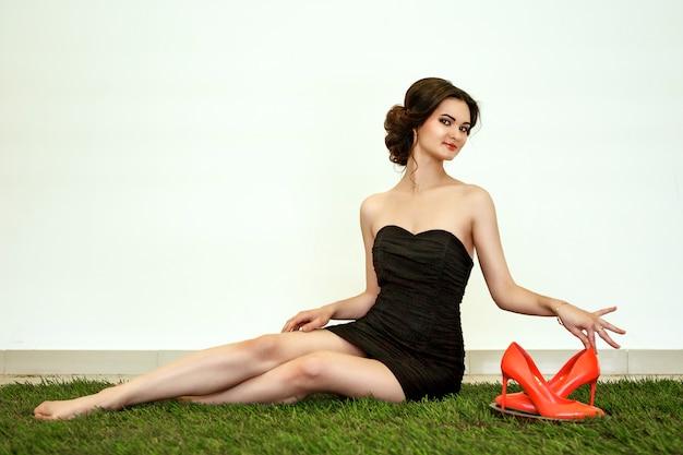 Модель позирует на траве с туфлями