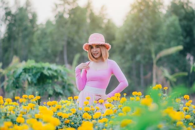 Модель стоит в цветочном саду, красивая женщина гуляет в саду календулы.