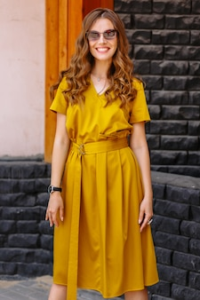 Model in a light yellow dress on the street