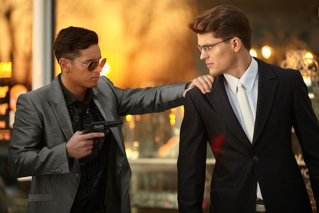 Model man with sunglasses and holding a gun in hand holding hostage onever young confident businessman.