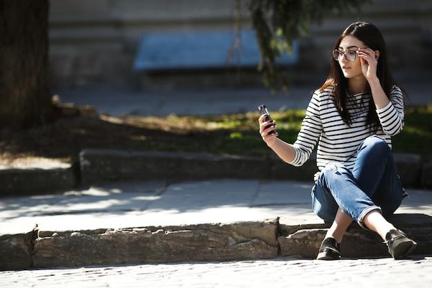 Modella in mezzo alla città con il telefono