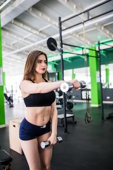 Modella in abbigliamento sportivo moderno con manubri fa il suo allenamento quotidiano in sportclub