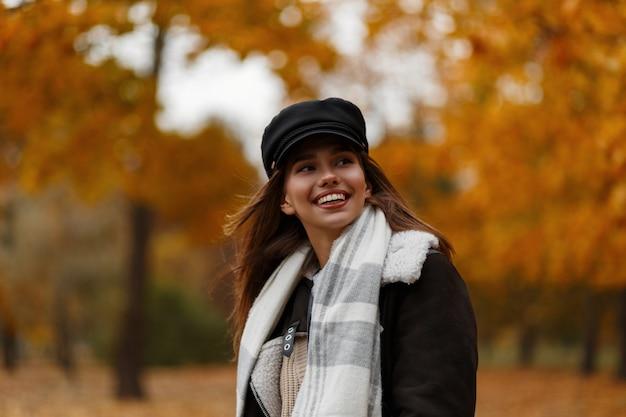 가을 숲에서 산책을위한 스카프에 갈색 재킷에 세련된 모자에 긍정적 인 젊은 여자의 모델. 귀여운 미소로 즐거운 소녀는 황금 단풍의 배경에 공원에서 쉬고 있습니다.