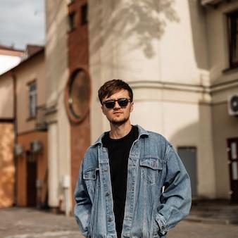 화창한 여름 날에 빈티지 건물 근처 블루 빈티지 재킷에 유행 선글라스에 세련 된 젊은 남자의 모델. 매력적인 남자가 도시의 마을을 여행합니다. 트렌디 한 남성 의류.