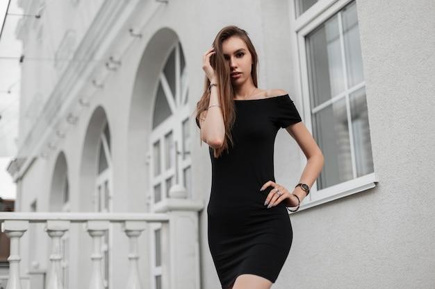 빈티지 화이트 건물 근처 거리에서 포즈 섹시 세련 된 검은 드레스에 긴 갈색 머리를 가진 세련 된 젊은 여자의 모델입니다. 유럽의 유행 소녀는 봄 날에 도시를 여행합니다.