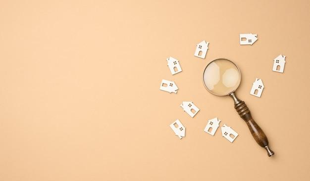 목조 주택 모델과 밝은 갈색 배경의 돋보기, 위쪽 전망. 임대, 구매, 모기지에 대한 홈 검색 개념