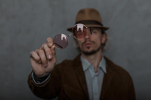 Модель молодого человека в элегантной одежде в стиле ретро в старомодной элегантной шляпе стоит и протягивает винтажные очки перед камерой в помещении. крутой красавчик парень. сосредоточьтесь на очках.