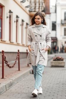 트렌치 코트에 젊은 여자와 니트 빈티지 스웨터의 모델은 거리를 산책