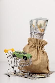돈 가방을 가진 자동차의 모델입니다. 수직 이미지
