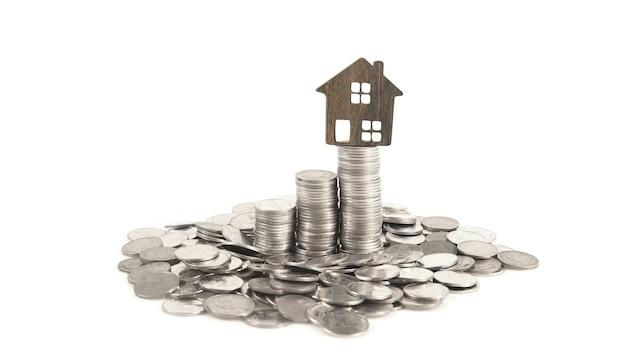 Макет отдельно стоящего миниатюрного домика на монетах. концепция инвестиций в недвижимость
