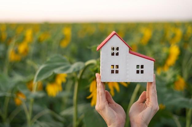 女性の手の中の家のモデル。環境にやさしい家のコンセプト。背景にひまわり。温室。