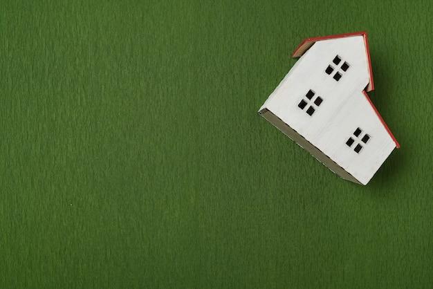 緑の背景に家のモデル。上面図。建設コンセプトのための土地の購入。