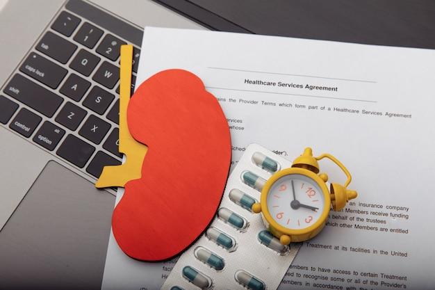 Модель почки, таблетки, будильник и контракт на здравоохранение, концепция ранней диагностики.