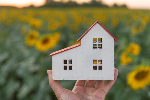 Модель небольшого белого дома в мужской руке.