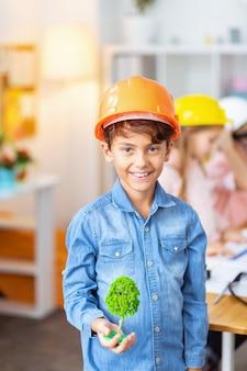 Модель дерева. темноволосый красивый мальчик в оранжевом шлеме держит маленькую модель дерева