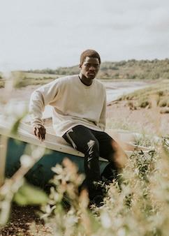 Modello in abbigliamento outdoor girato su una barca sulla costa