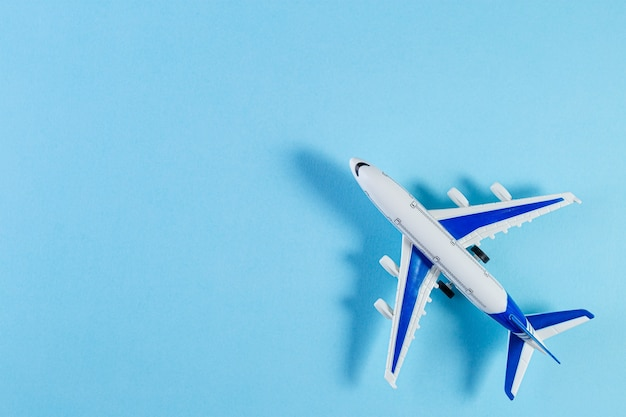 Model plane, airplane on blue pastel color background. flat lay of miniature toy airplane. minimal trip and travel creative concepts. copy space
