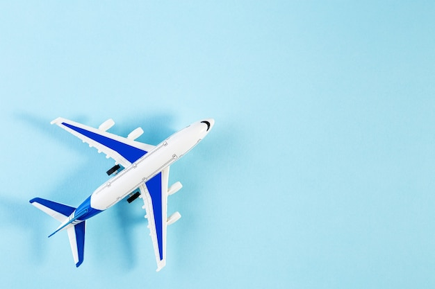 Model plane, airplane on blue pastel color background. summer travel or vacation concept. flat lay of miniature toy airplane. trendy minimal style, copy space