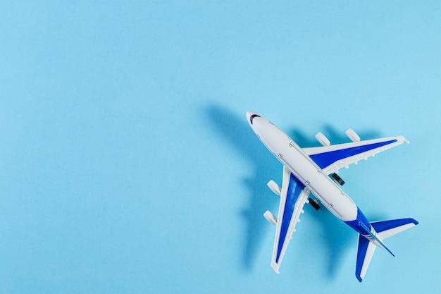 Модель самолета, самолет на синем фоне пастельных тонов. плоская планировка миниатюрного игрушечного самолетика. минимальные поездки и творческие концепции путешествий. копировать пространство