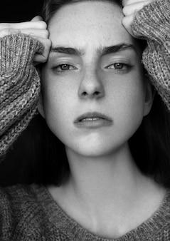 Модельное испытание портрета при молодая красивая фотомодель нося серый шлямбур на черной предпосылке драматический портрет.