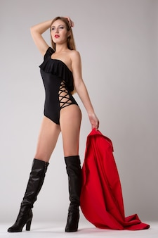The model poses in a black bodysuit and holding a bright red raincoat in her hand