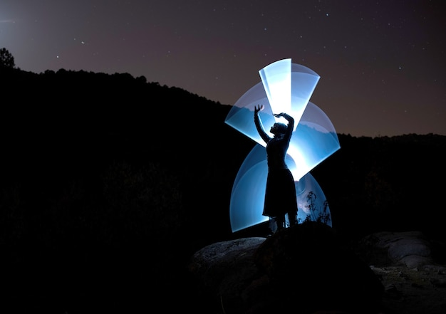 夜にポーズをとり、懐中電灯だけで光を描く技法で照らされたモデル。