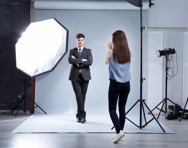 スタジオでプロの写真家のためにポーズをとるモデル